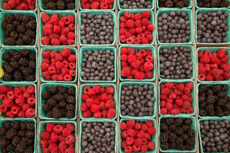Berries raspberries blueberries and blackberries in a row on green boxes at market photo