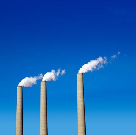 Chimney white smoke three in a row on a blue sky photo
