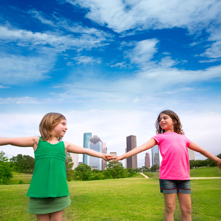 Two sister girls friends playing holding hand in urban modern skyline on park lawn photo