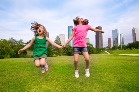 Two sister girls friends jumping happy holding hand in urban modern skyline on park lawn photo