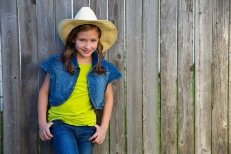 Children girl as kid cowboy girl cowgirl posing on wooden fence far west style Stock Photo - 22531567