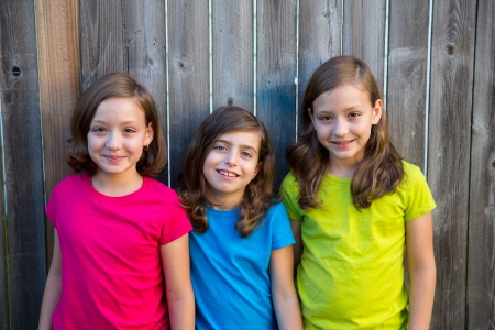 dido: Sister and friends kid girls portrait smiling happy on gray fence wood backyard
