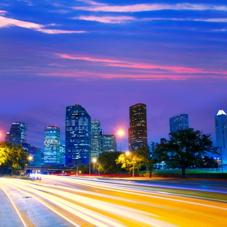 gloaming: Houston Texas modern skyline at sunset twilight with traffic headlights lights trace Stock Photo