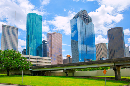 rise and shine: Houston Texas Skyline with modern skyscapers and blue sky view from park lawn
