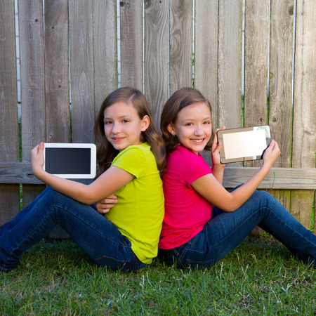 twin sister: Twin sister girls playing with tablet pc sitting on backyard lawn fence leaning on her back