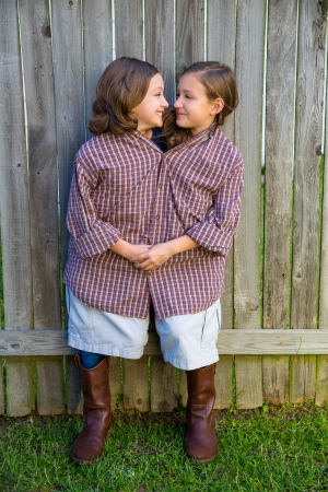 twin girls fancy dressed up pretending be siamese with his father shirt looking eachother photo