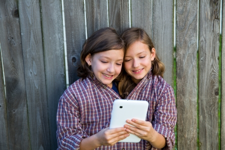 dido: twin girls fancy dressed up pretending be siamese with dad shirt playing with tablet pc