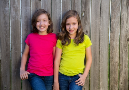 dido: Twin sisters with different hairstyle posing on wood backyard fence