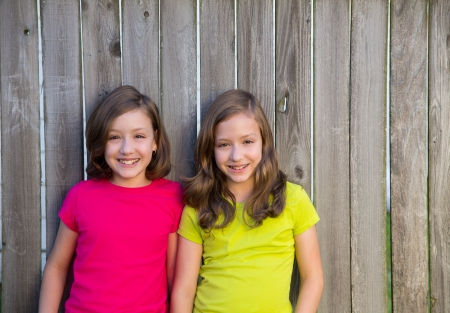 Twin sisters with different hairstyle posing on wood backyard fence photo