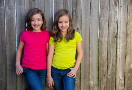 niñas gemelas: Niñas hermanas gemelas con diferente peinado posando en la madera cerca del patio trasero Foto de archivo