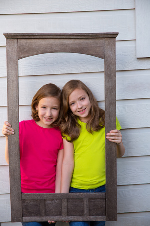 dido: Twin sister girls posing with aged wooden border frame on white wall