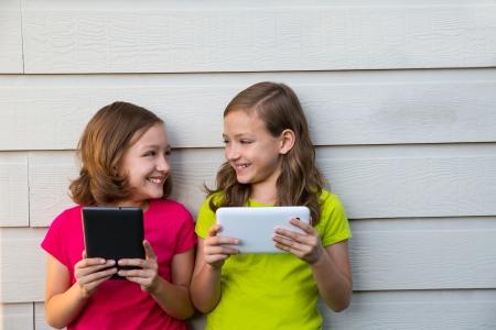 soeur jumelle: Les filles jumelles de soeur jouant avec la tablette pc heureux sur un mur blanc en regardant les uns les autres