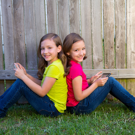 Twin sister girls playing with tablet pc sitting on backyard lawn fence leaning on her back photo