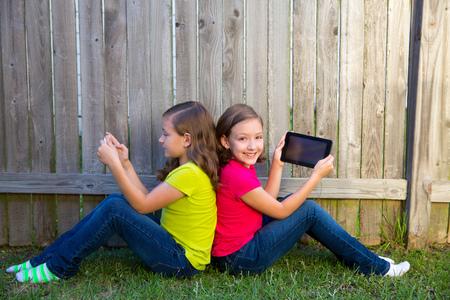 soeur jumelle: Les filles jumelles de soeur jouant avec tablet pc assis sur cour cl�ture de la pelouse se penchant sur son dos