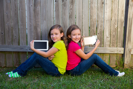 soeur jumelle: Filles jumelles de soeur jouant avec la tablette pc assis sur cour pelouse cl�ture en s'appuyant sur son dos Banque d'images