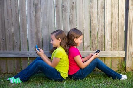 soeur jumelle: Twin Sister filles jouant avec le smartphone assis sur cour pelouse cl�ture en s'appuyant sur son dos