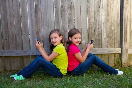 soeur jumelle: Filles jumelles de soeur jouant avec le smartphone assis sur cour pelouse cl�ture en s'appuyant sur son dos Banque d'images