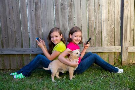 soeur jumelle: Les filles jumelles de soeur jouant avec un chien smartphone et chihuahua assis sur cour