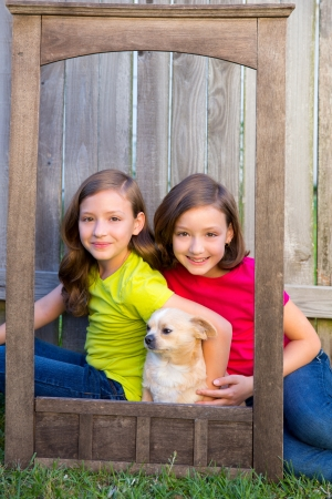 Twin sisters portrait with chihuahua dog on grunge wood border frame sitting on lawn photo