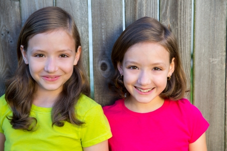 Happy twin sisters with different hairstyle smiling on wood backyard fence photo