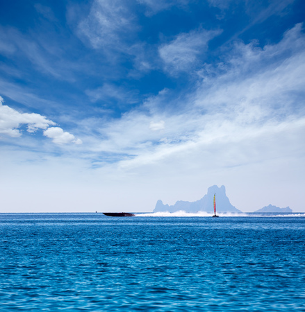 Es Vedra Ibiza silhouette with boats view from Formentera in Balearic islands photo