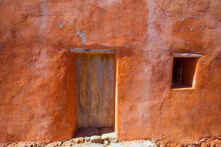 ocher: Ibiza grunge orange facade in Benirras beach at Balearic Islands Spain Stock Photo