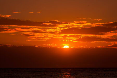 over the sea: Sunset orange sky at evening over sea with clouds Stock Photo