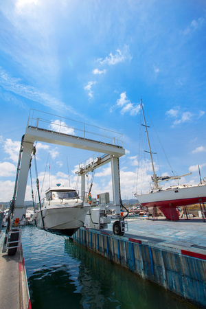 boat lift: Boat crane working with boats in Mediterranean Stock Photo