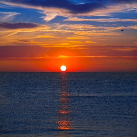 Sunset at Mediterranean sea with orange sky and sun reflection photo