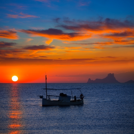 ibiza: Ibiza sunset Es Vedra view and menorquina fisherboat from Formentera orange sky Stock Photo