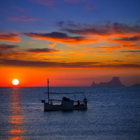 baleares: Ibiza sunset Es Vedra view and menorquina fisherboat from Formentera orange sky Stock Photo