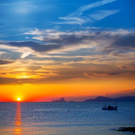 vedra: Ibiza sunset Es Vedra view and menorquina fisherboat from Formentera orange sky Stock Photo