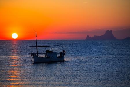 es: Ibiza sunset Es Vedra view and menorquina fisherboat from Formentera orange sky Stock Photo