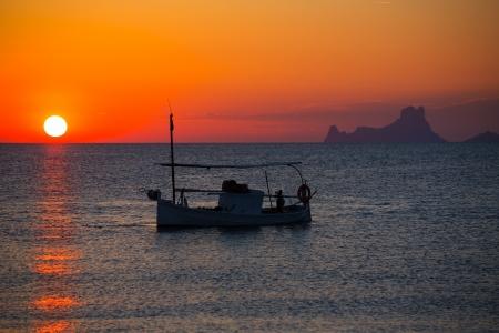 Ibiza sunset Es Vedra view and menorquina fisherboat from Formentera orange sky photo