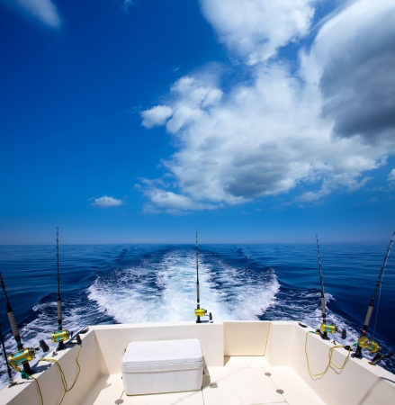 Fishing boat stern deck with trolling fishing rods and reels in blue ocean sea Stockfoto