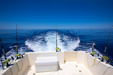 fishing tackle: Fishing boat stern deck with trolling fishing rods and reels in blue ocean sea Stock Photo