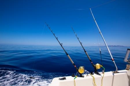 atún: Ibiza barco de pesca curricán con cañas y carretes en color azul mar Mediterráneo Baleares