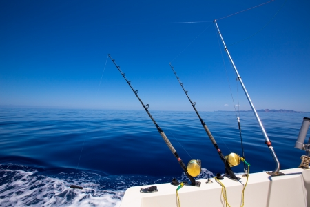 Ibiza fishing boat trolling with rods and reels in blue Mediterranean sea Balearic Stockfoto