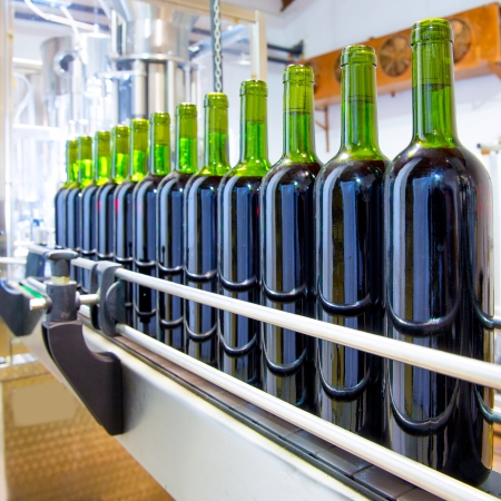 red wine in glass bottling machine at winery Stock Photo