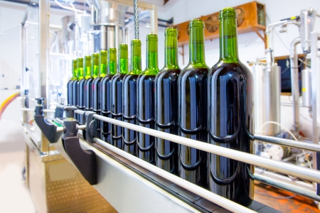 machine: red wine in glass bottling machine at winery Stock Photo