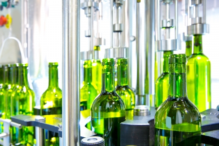 white wine in glass bottling machine at winery photo