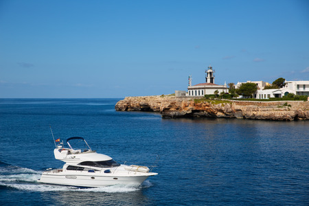 Ciutadella Sa Farola Lighthouse with yatch boat in Balearic islands photo