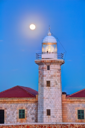 Ciutadella Menorca Punta Nati lighthouse with moon shining in sky photo