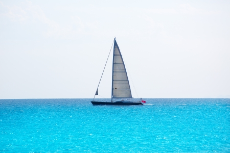 Sailboat sailing in balearic islands turquoise waters of Mediterranean sea photo