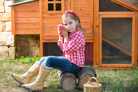 coop: breeder hens kid girl rancher blond farmer playing with chicks in chicken tractor coop