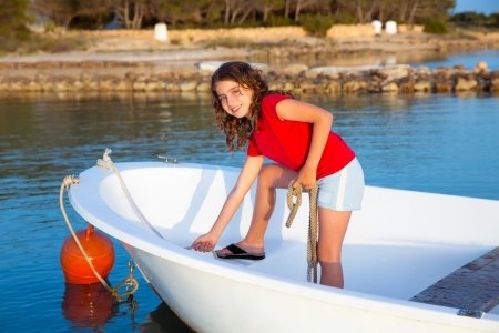Kid girl pretending to be a sailor in boat bow at Formentera Balearic Islands photo