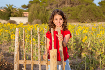 Smiling farmer girl with sunflowers field holding fence door in Mediterranean photo