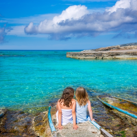 Blond and brunette kid sister girls sitting on beach port in Formentera summer vacation photo