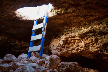 Cave hole entrance with ladder in Barbaria Cape at formentera photo