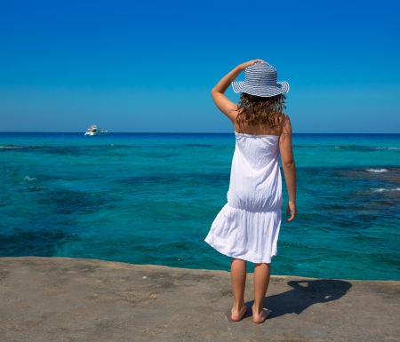 Girl rear view in Formentera Ibiza beach turquoise Mediterranean sea background photo